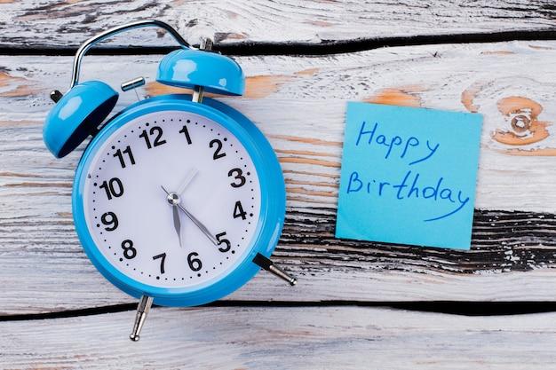 Sveglia vintage blu e carta con slogan di buon compleanno. tavolo in legno bianco sullo sfondo.