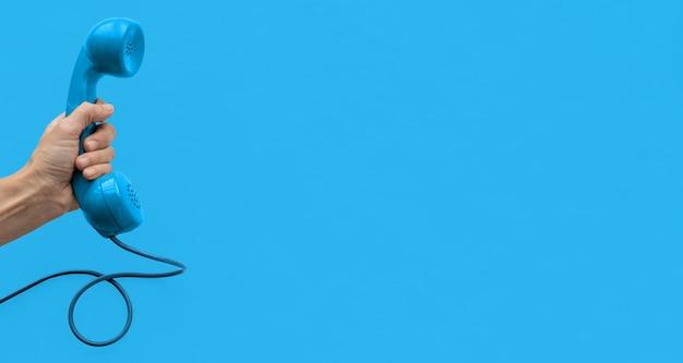 Una cornetta del telefono con linea vintage blu con una mano e sfondo blu.