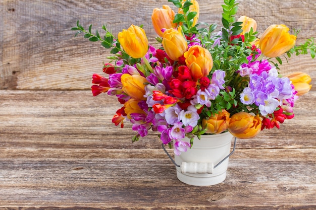 Fresia blu, viola e rossa e fiori di tulipano arancione sulla tavola di legno