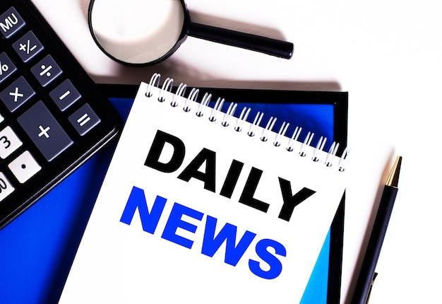 Su una parete blu, vicino alla calcolatrice, lente d'ingrandimento e penna, un taccuino con la scritta daily news