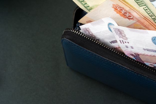 Portafoglio blu pieno di soldi, rubli russi e dollari usa