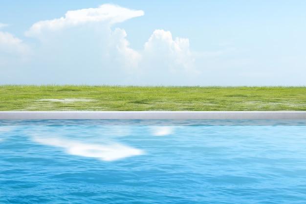 Acqua blu sullo stagno con erba verde e uno sfondo di cielo blu