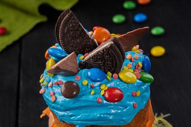 Albumi montati a neve blu con dolci su torta di pasqua