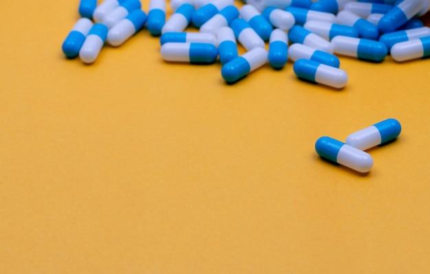 Pillole di capsule antibiotiche blu e bianche sparse su sfondo giallo resistenza ai farmaci antibiotici
