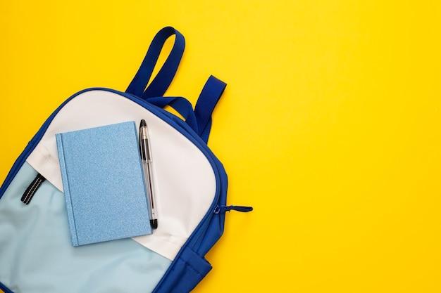 Zaino blu e bianco su sfondo giallo