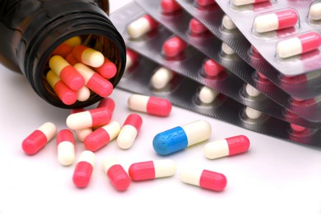 Capsula blu e bianca in un gruppo di capsule rosa e bianche.