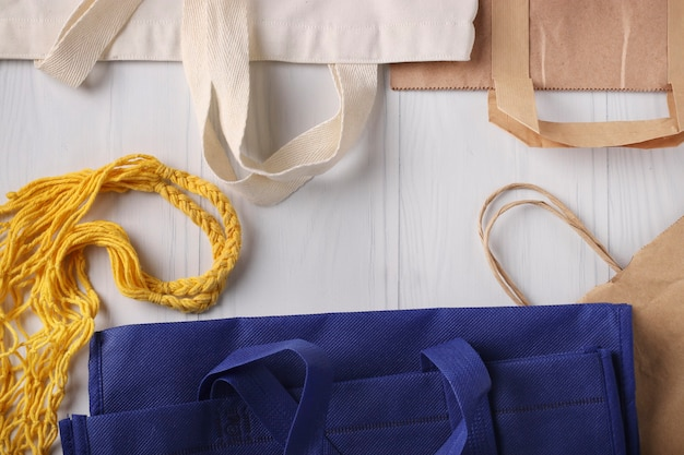 Borse per la spesa blu e bianche, borsa a rete gialla e sacchetti di carta per prodotti su sfondo bianco, concetto di rifiuti zero, vista dall'alto