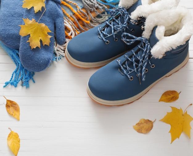 Scarpe e guanti blu di inverno su fondo di legno bianco