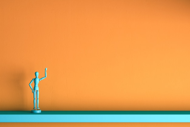 L'uomo di legno blu presenta una cosa invisibile sullo spazio della copia della parete arancione per il tuo oggetto o testo