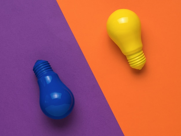 Lampadine blu e gialle su uno sfondo arancione e viola. minimalismo. disposizione piatta.