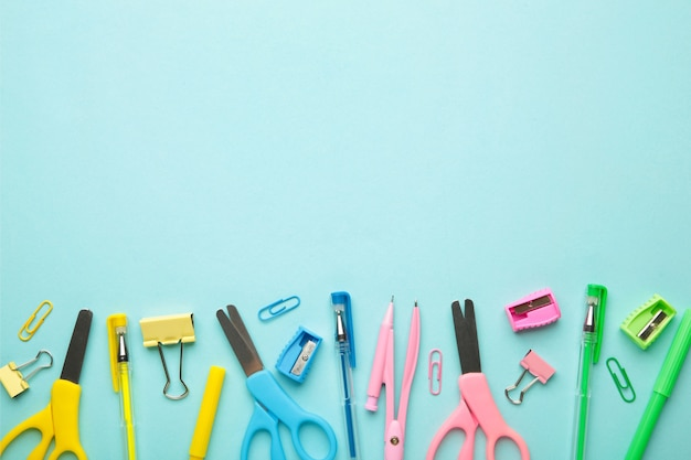 Materiale scolastico blu, giallo, rosa, verde su sfondo blu. torna al concetto di scuola. vista dall'alto.