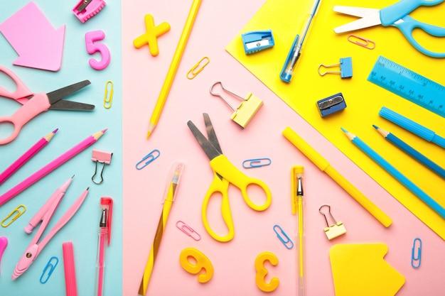 Materiale scolastico blu, giallo, rosa, verde su sfondo colorato. torna al concetto di scuola. vista dall'alto.