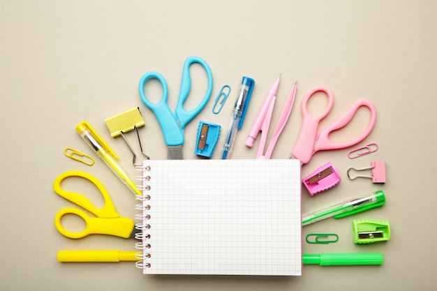 Materiale scolastico blu, giallo, rosa, verde con taccuino su sfondo grigio. torna al concetto di scuola.