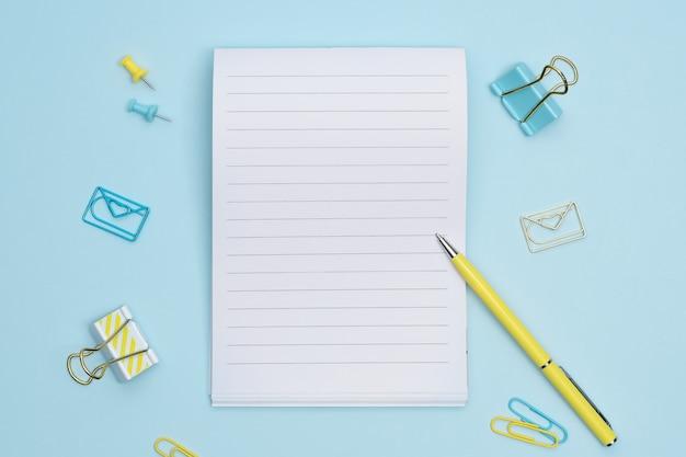 Oggetti e taccuino fissi blu e gialli su fondo blu con lo spazio della copia. taccuino vuoto per note o lista di controllo.