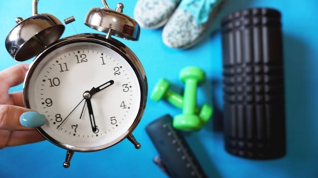 Tappetino yoga blu, due manubri, sveglia, rotolo automassaggio, scarpe da ginnastica e borraccia - tempo per lo sport