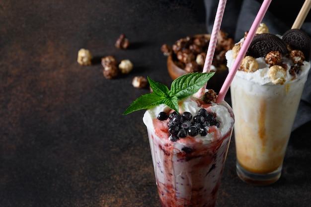 Milkshake blueberrie guarnito con panna montata, biscotti, marmellata gocciolante e menta