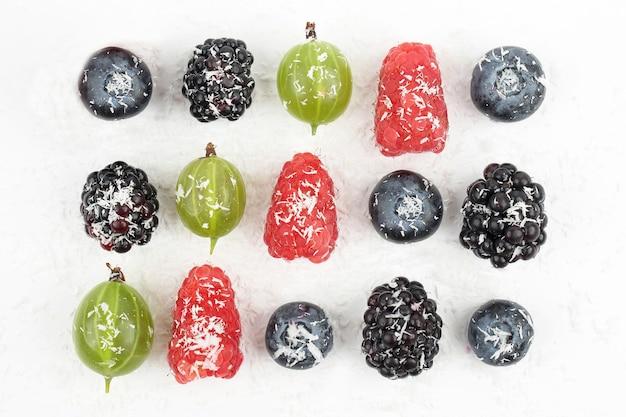 Mirtilli, more, uva spina e lamponi cosparsi di cocco su sfondo bianco. verdure fresche e cibo sano