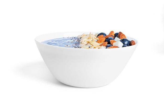 Dessert di mirtilli con frutta, mandorle e semi di chia isolati su sfondo bianco. ciotola per frullato blu con frutti di bosco. foto di alta qualità