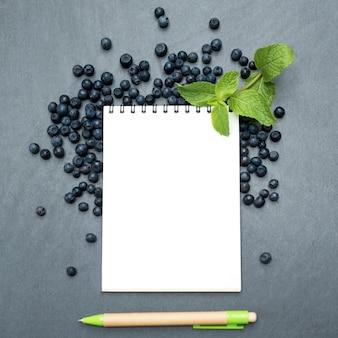 Mirtilli, foglie di menta e blocco note per scrivere appunti o risoluzioni