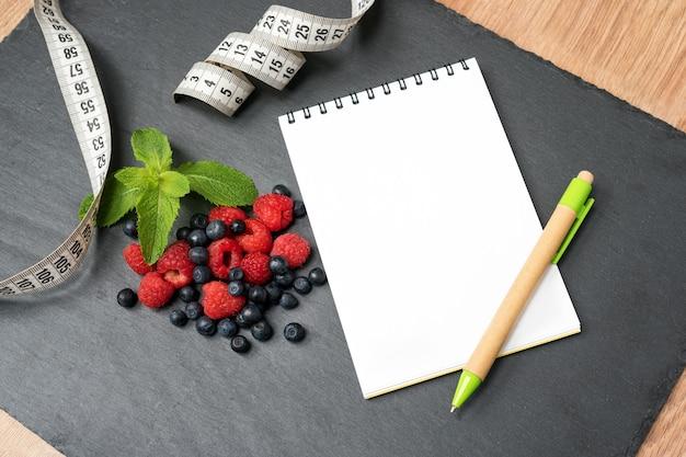 Mirtilli, lamponi, menta, metro a nastro e blocco note per scrivere appunti