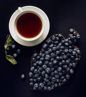 Mirtilli su un piatto di legno, una tazza di tè e foglie essiccate di melis su uno spazio buio, natura morta, vista dall'alto