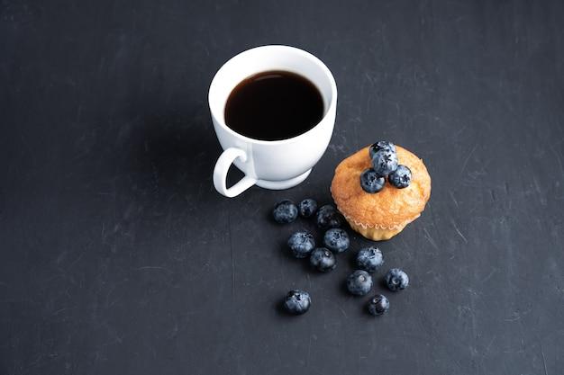 Superfood organico antiossidante al mirtillo e muffin dolce con tazza di caffè concetto per mangiare sano e nutrizione dietetica vista dall'alto su sfondo nero scuro
