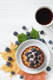 Torta di mirtilli con frutti di bosco freschi e tazza di caffè e foglie di acero autunnali