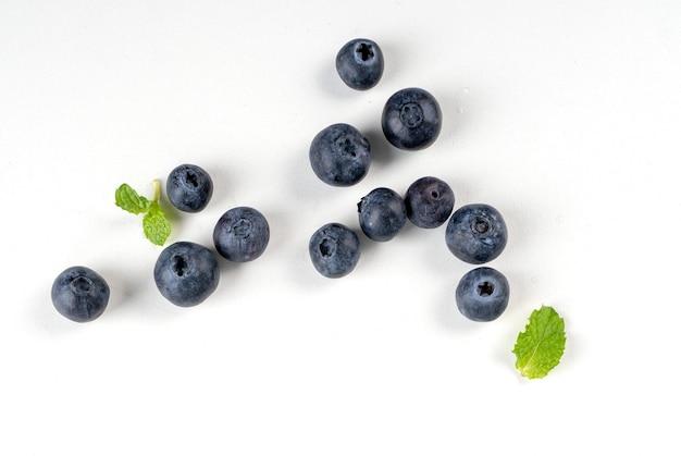 Vista dall'alto di frutti di mirtillo isolata su uno sfondo bianco, disposizione sopraelevata piatta con foglia di menta, concetto di design sano.