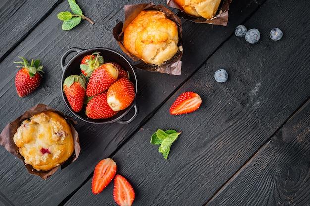 Muffin ai mirtilli, su sfondo di tavolo in legno nero, vista dall'alto piatta con spazio di copia per il testo