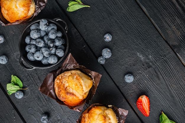 Muffin ai mirtilli con frutti di bosco freschi, sul tavolo in legno nero tavolo, vista dall'alto laici piatta