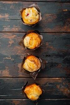 Muffin ai mirtilli con frutti di bosco freschi, sul vecchio tavolo in legno scuro, vista dall'alto laici piatta