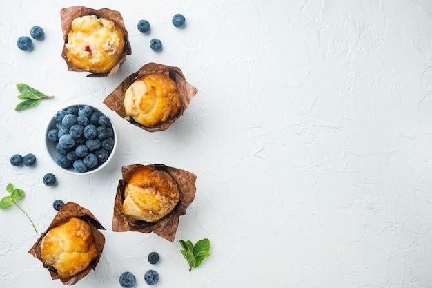 Muffin ai mirtilli con frutti di bosco freschi, sul tavolo bianco, vista dall'alto laici piatta