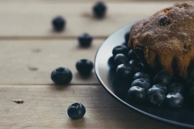 Muffin ai mirtilli con zucchero a velo e frutti di bosco freschi. i mirtilli freschi sono sparsi sul tavolo di legno