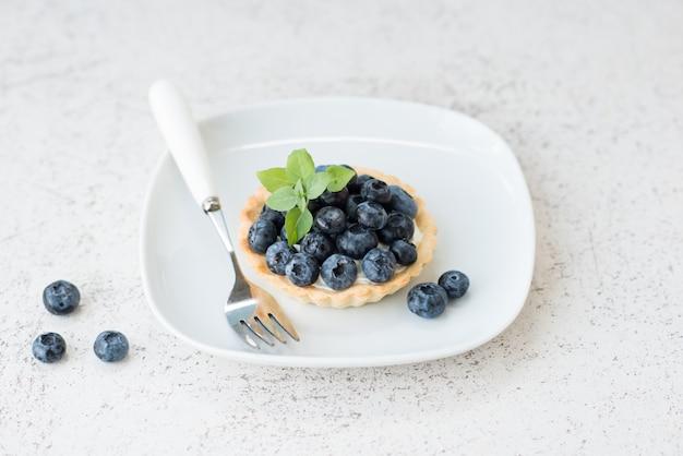 Crostata di mirtilli con crema, torta di formaggio con frutti di bosco su un piatto