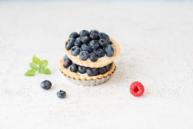 Crostata di mirtilli con panna, cheesecake con frutti di bosco su bianco