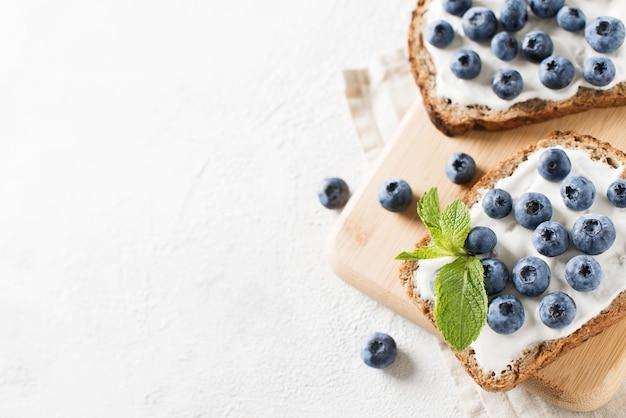 Toast ai mirtilli a colazione su sfondo bianco. cibo salutare