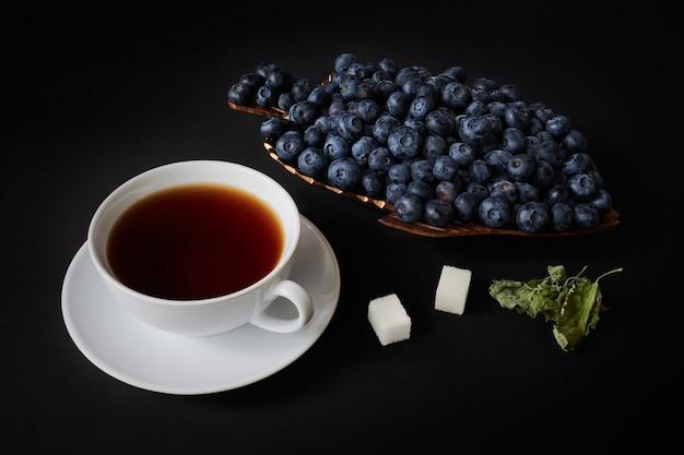 Mirtillo su un piatto di legno, tazza con tè, zucchero e foglie secche di mellisa su uno spazio buio, natura morta