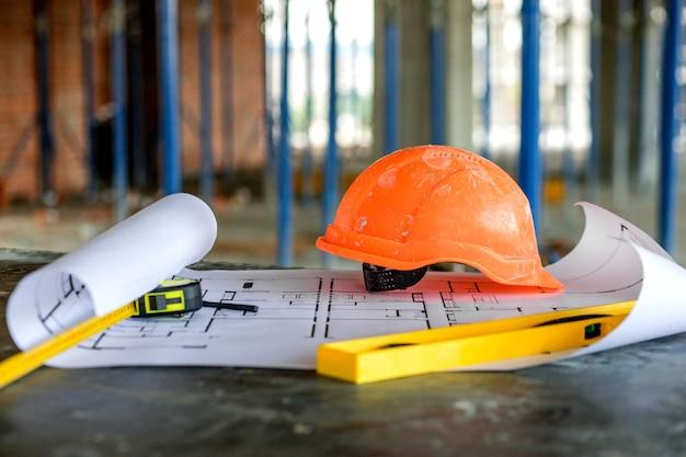Progetto di progetti di cianografie, livello di costruzione e casco, primo piano. concetto di costruzione.