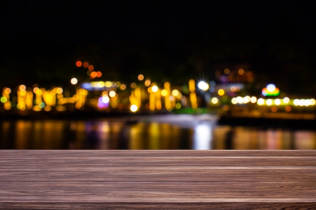 Sfocatura caffè ristorante o resort vicino al mare di tavolo in legno scuro con sfondo bokeh oro chiaro