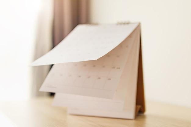 Sfocatura foglio sfocatura pagina calendario su tavola di legno sfondo pianificazione pianificazione aziendale