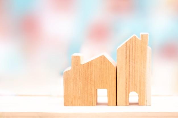 Sfocatura casa in legno vuota su sfondo sfocato. tempo di investire, immobiliare e concetto di proprietà. risparmio finanziario e concetto di investimento. Foto Premium