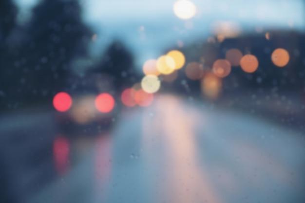 Sfocatura immagine di luce auto di notte mentre piove