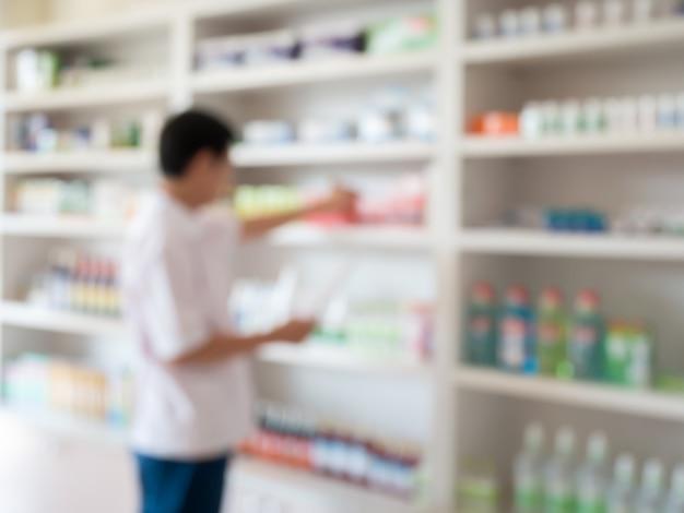 Sfocatura dell'immagine del farmacista che prende medicine dallo scaffale in farmacia
