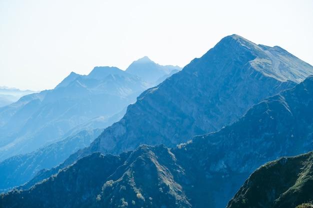 Sfondo naturale astratto sfocato con montagne del caucaso in una nebbia blu mattina