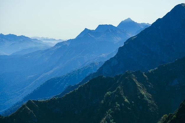 Sfondo naturale astratto sfocato con montagne in una nebbia blu mattina