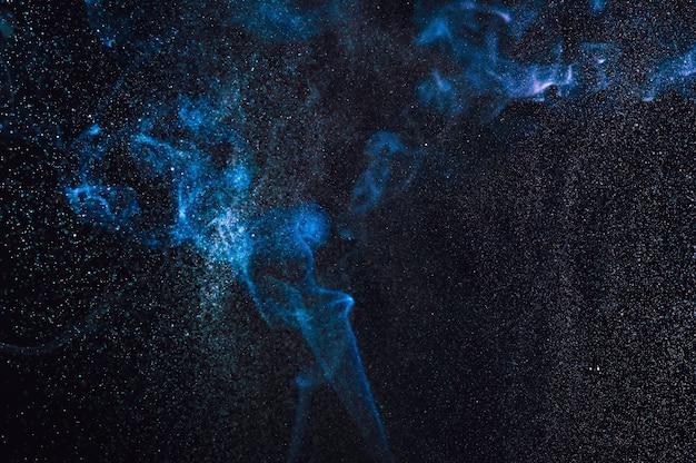 Fumo astratto sfocato e spruzzi d'acqua su uno sfondo nero