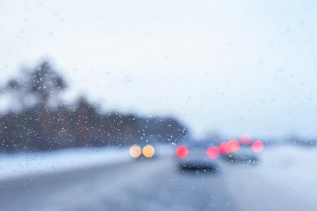 Sfondo sfocato del parabrezza di un'auto con fiocchi di neve e automobili sullo sfondo