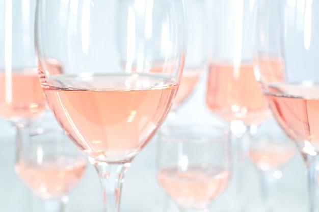 Sfondo sfocato di molti bicchieri diversi con vino rosato.