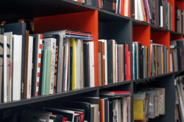 Sfondo sfocato con libri e cataloghi multicolori sugli scaffali.