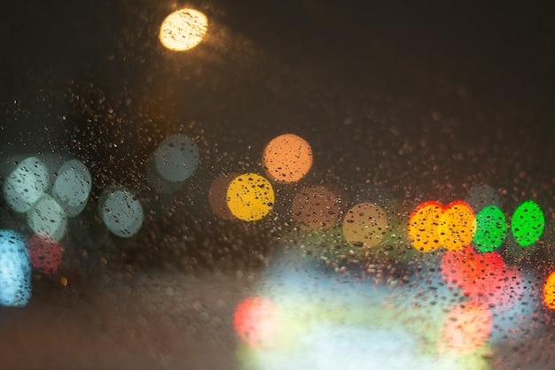 Sfondo sfocato con gocce di pioggia e luci.